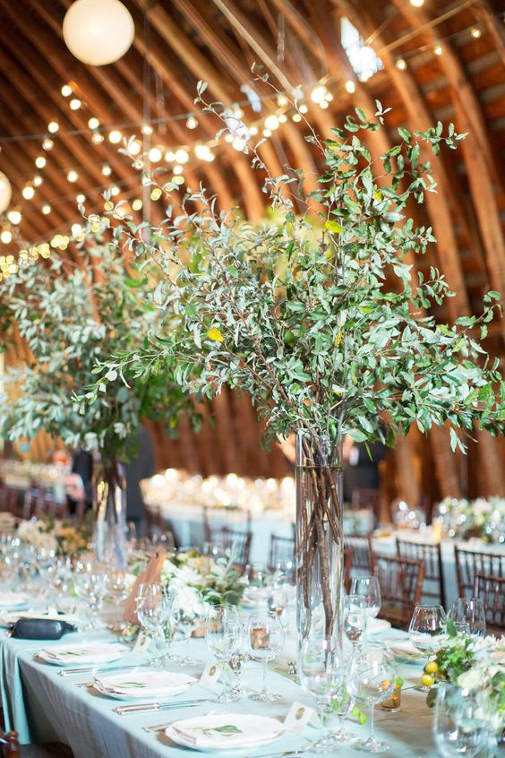 barn wedding centerpieces of tall clear vases with greenery branches look chic and very modern