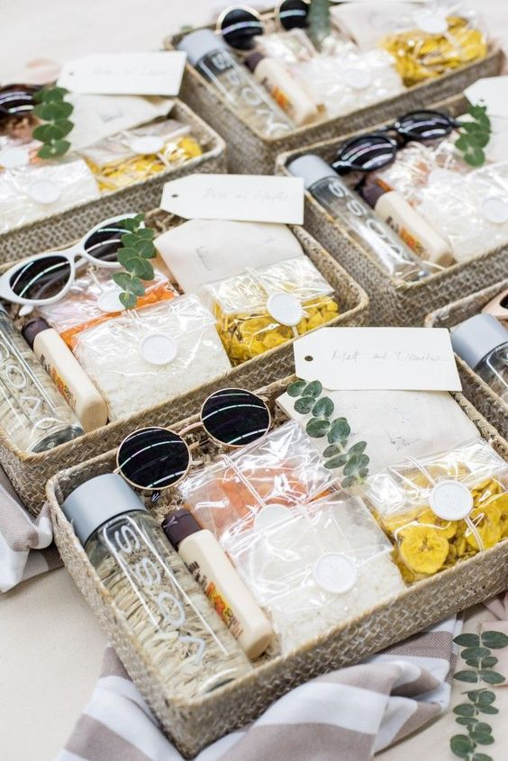 beach bridal shower welcome baskets with sunglasses, water bottles, some dried snacks, greenery and sunscreen