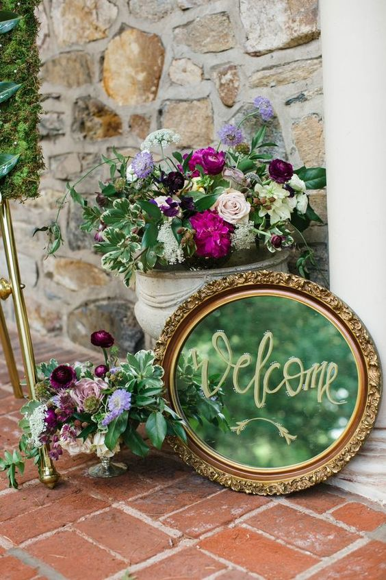 bold floral arrangements in vintage urns, a vintage mirror in a chic frame are a great decoration for a garden bridal shower