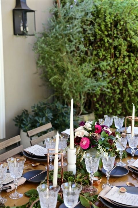 lush table decor with graphite grey plates, bold blooms, crystal glasses and candles plus greenery for a fall garden shower