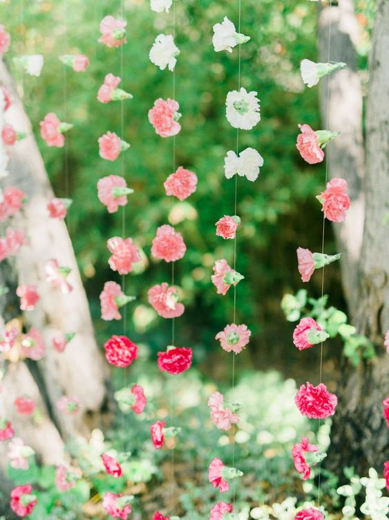 ombre white to pink and fuchsia flower garlands over the space is a lovely and bold idea for a garden bridal shower