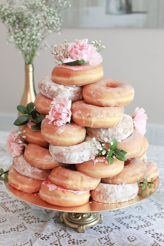 skip a bridal shower cake and go for a stack of donuts decorated with pink blooms and baby's breath