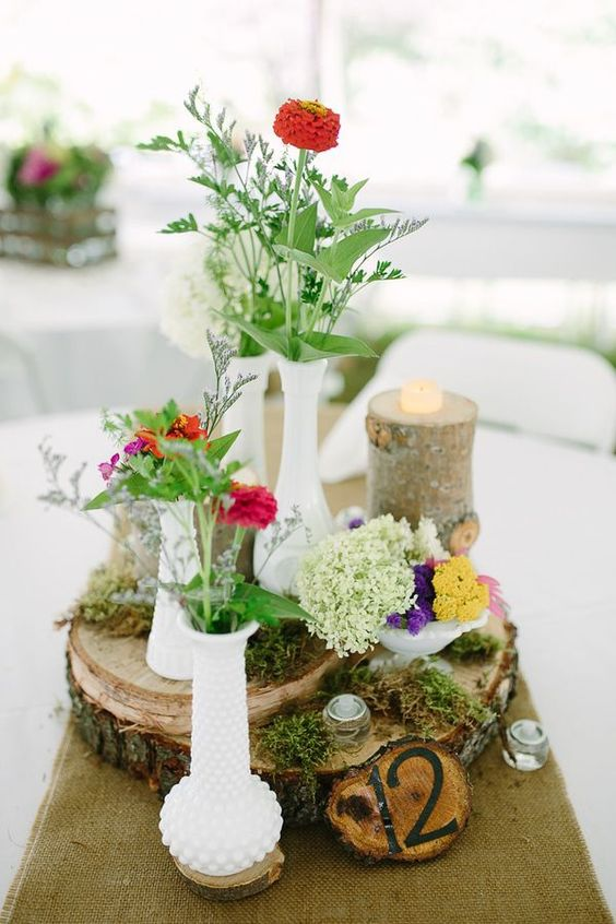 wood slices with moss, bright blooms in milk glass vases, a rustic table number and a candle on a tree stump