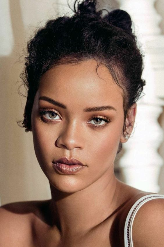 Rihanna wearing smokey eyes, a dusty pink shiny lip, a touch of blush and highlighter looks super chic