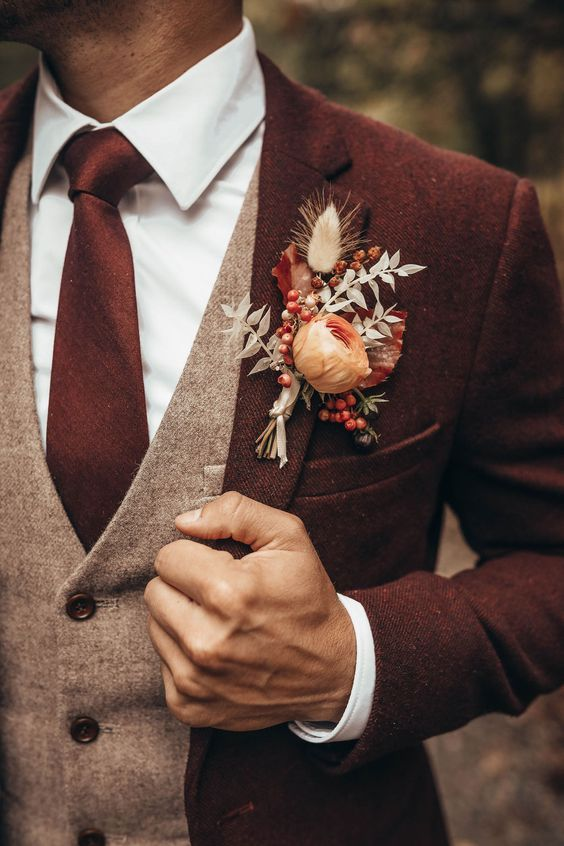 a beautiful fall wedding boutonniere with berries, white and burgundy leaves, a peachy bloom is very refined and cool