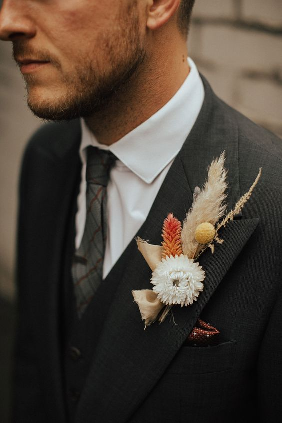 a beautiful fall wedding boutonniere with pampas grass, billy balls, a white bloom and an orange piece plus a tan bow
