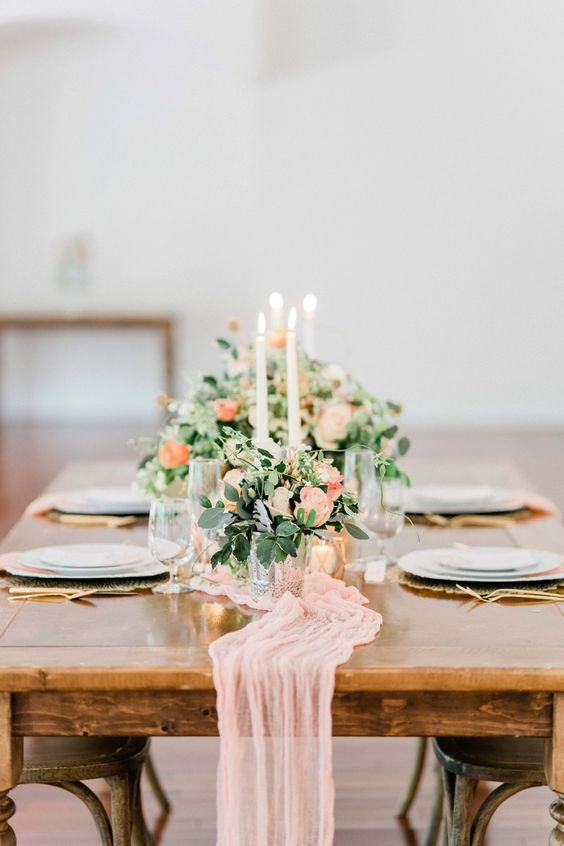 a beautiful peach and cream wedding tablescape with a peachy table runner and blooms, greenery and candles plus gold cutlery