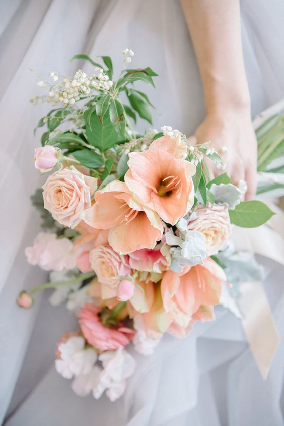 a beautiful peachy and white bloom wedding bouquet with greenery and lily of the valley is romantic