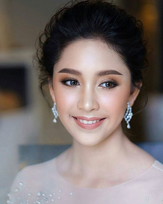 a beautiful statement makeup with a glossy pink lip, pink blushes, brown smokeys and statement eyebrows for a formal wedding