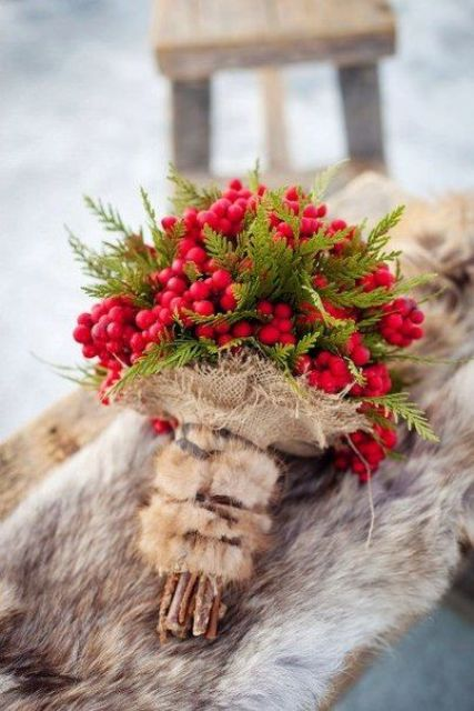 a berry and evergreen wedding bouquet with a fur and burlap wrap is a bold idea for a rustic winter bride