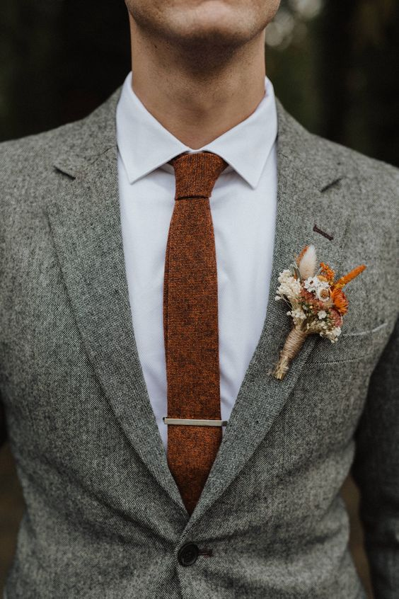 a boho wedding boutonniere with white and rust blooms and herbs that matches the rust-colored tie