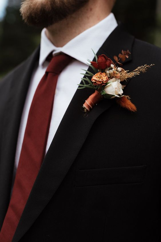 a bold fall-colored wedding boutonniere with burgundy and rust blooms, greenery and dried foliage and grass