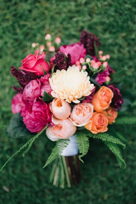 a bold fall wedding bouquet of blush, hot pink peonies and roses, greenery and ferns is a gorgeous color statement