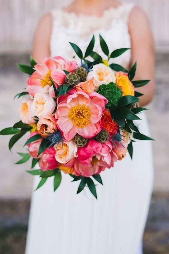 a bold wedding bouquet of coral, yellow and orange blooms, seed pods, succulents and greenery is ideal for a bright summer wedding