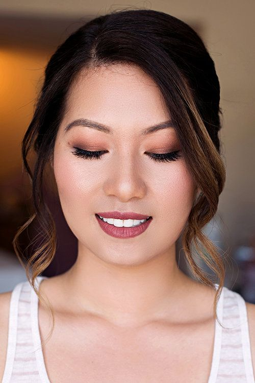 a bold wedding makeup with a metta purple lip, brown smokeys, extended eyelashes and blushes