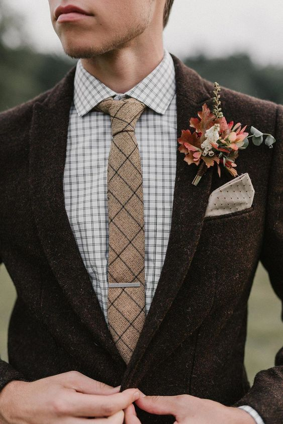 a bright and cool fall wedding boutonniere with colorful fall leaves, berries, white blooms looks very rustic like