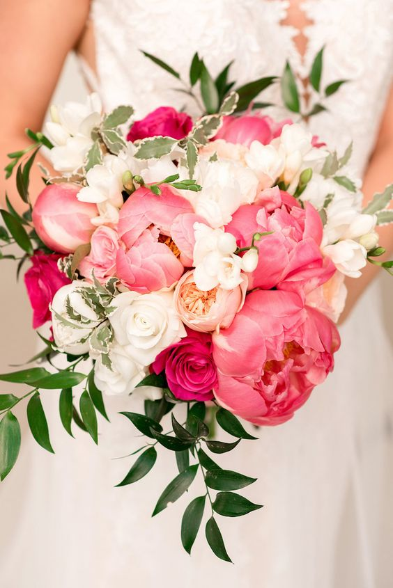 a bright and cool wedding bouquet of white, blush and coral pink peonies and greenery is amazing for spring or summer