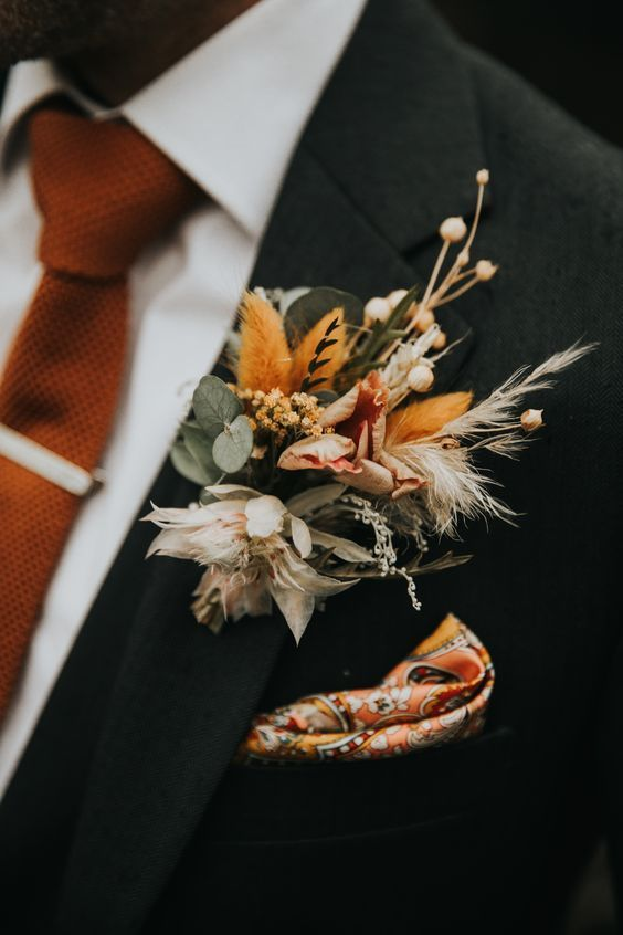a bright dried flower, grass and elaves boutonniere will add a refined and bold touch to the outfit