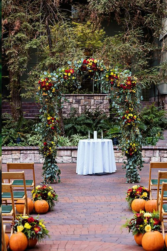a bright rustic fall wedding aisle with pumpkins, colorful blooms and greeneyr and a matching arch done with the same blooms