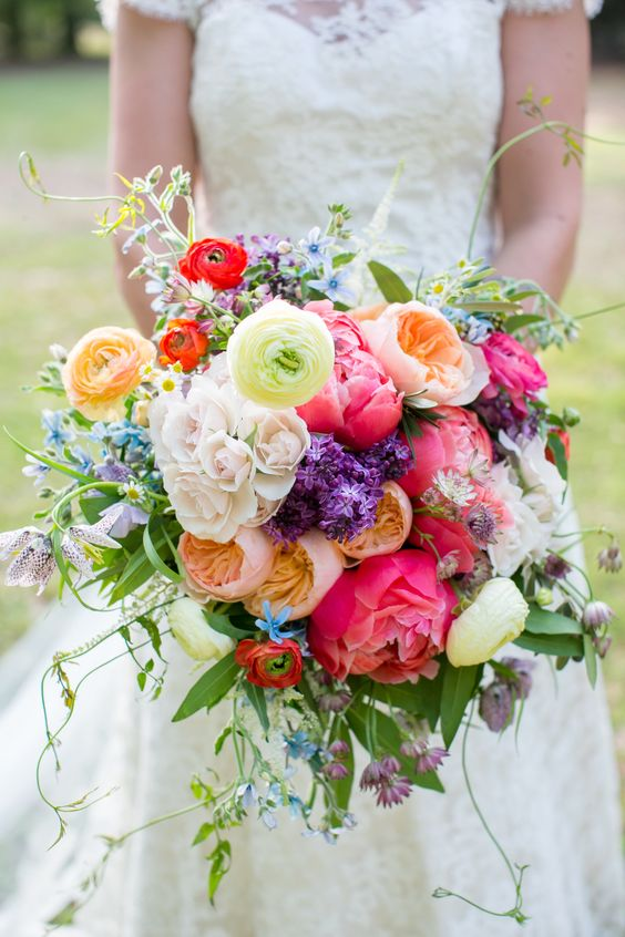 a bright wedding bouquet of coral and peachy peonies, white and yellow blooms, lilac, blue blooms and greenery is amazing