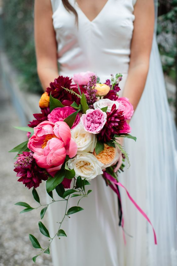 a bright wedding bouquet of deep purple dahlias, pink peonies and white ones, greenery and ribbons for a bold summer wedding
