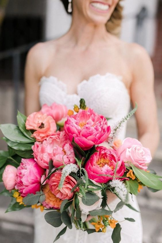 a bright wedding bouquet of pink and hot pink peonies and greenery, yellow blooms and astilbe is a fun idea for a summer bride