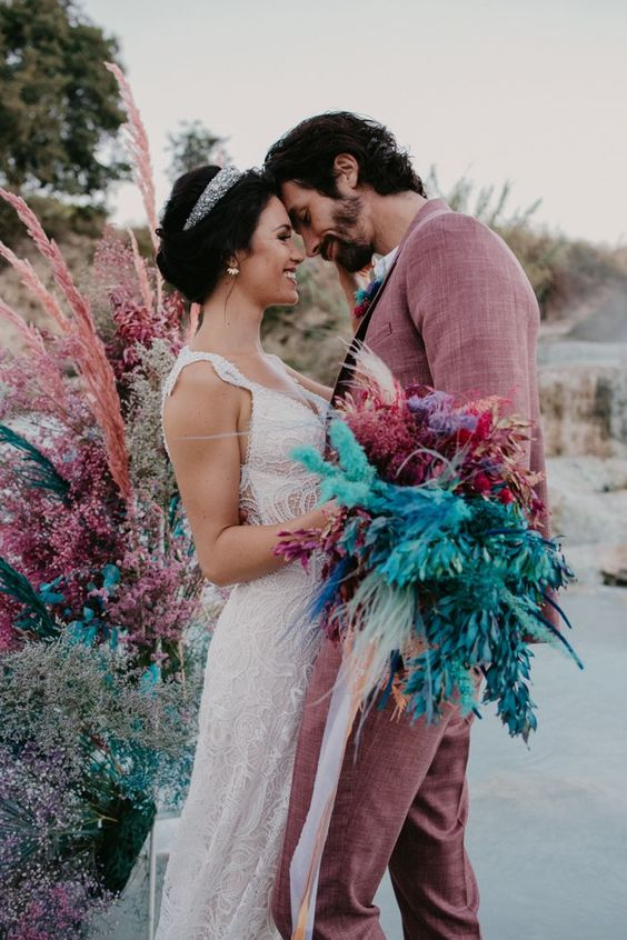 a bright wedding bouquet of spray painted feathers and pampas grass, ostrich feathers and sheer ribbons is a bold idea
