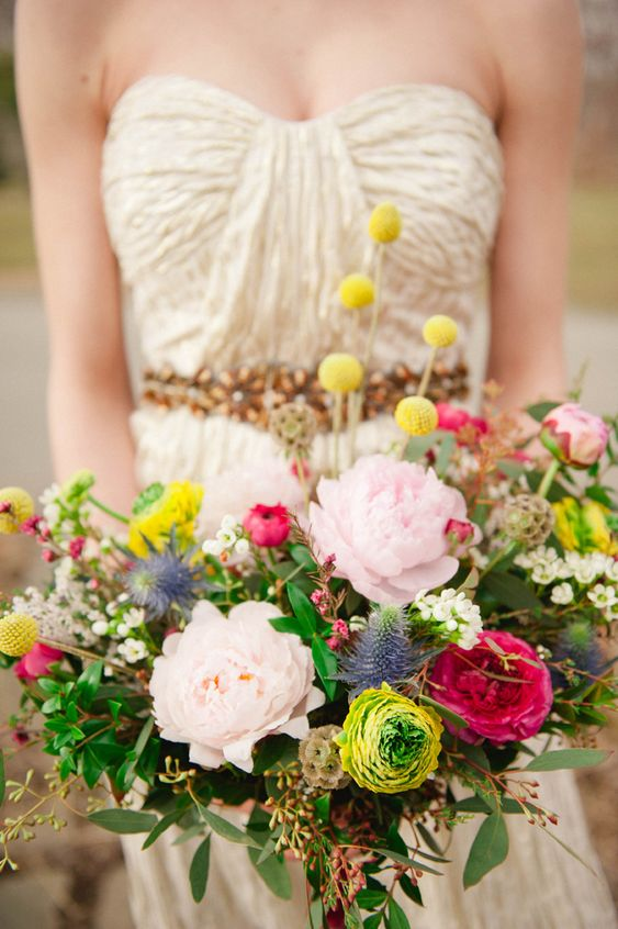 a bright wedding bouquet with blush peonies, hot pink and yellow blooms, billy balls, thistles and greenery for summer
