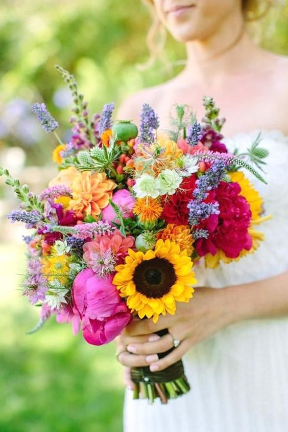 a bright wedding bouquet with hot pink peonies, sunflowers, lilac and orange blooms and astilbe for a summer bride