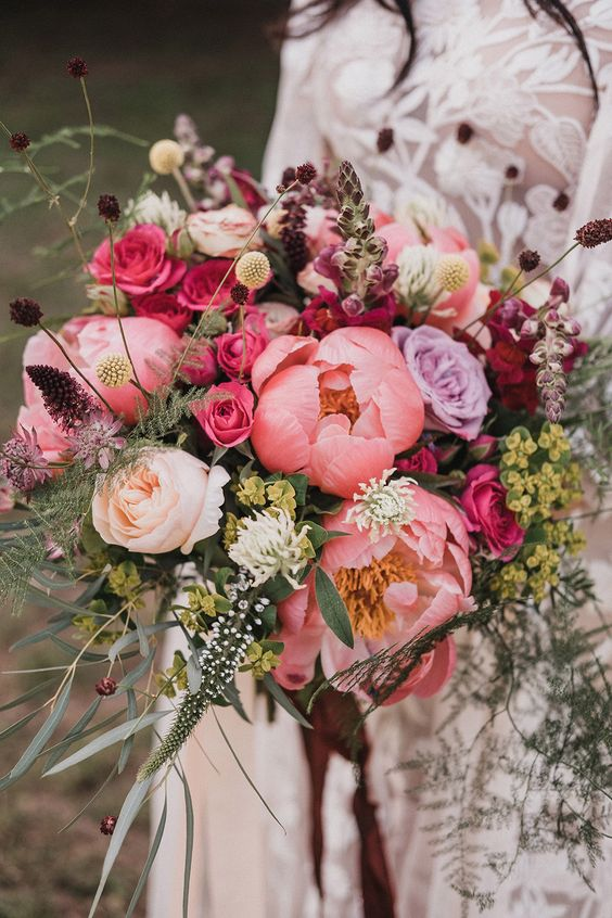 a cheerful and bright wedding bouquet with pink peonies, hot pink roses, various fillers, greenery and other stuff for a fall wedding