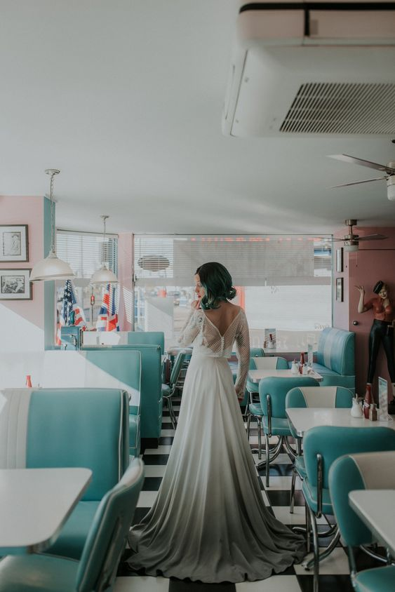 a chic A-line wedding dress in white and grey, with an open back and long illusion sleeves plus green hair