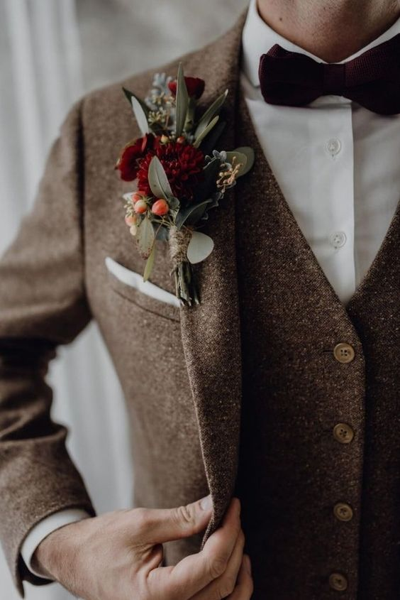 a chic fall wedding boutonniere with burgundy blooms, berries and greenery will be a lovely colorful touch to the look