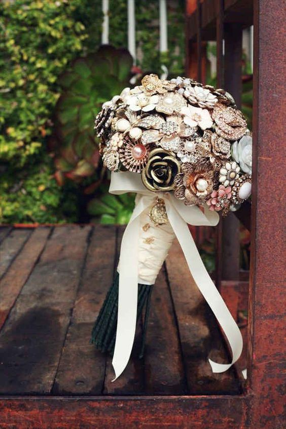 a chic vintage brooch wedding bouquet with a ribbon wrap and a bow is a very chic and elegant idea for a vintage-loving bride