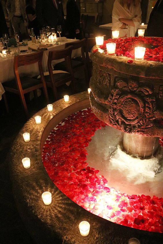 a chic vintage fountain with floating red blooms and candles on the edge is a stylish and lovely idea to go for