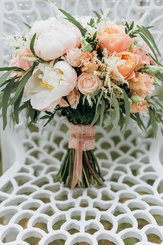 a chic wedding bouquet with peachy, pink and white blooms and greenery plus pink lace wrap and ribbons