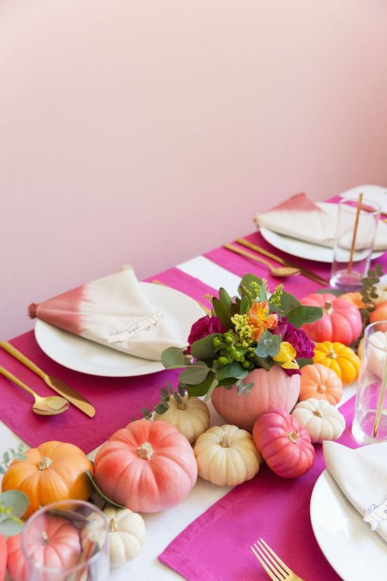 a colorful fall tablescape with bright painted pumpkins, blooms and dip dye napkins