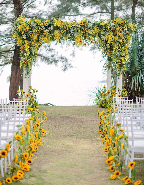 a colorful fall wedding aisle lined up with bold sunflowers and with a matchign wedding arch covered with them, too