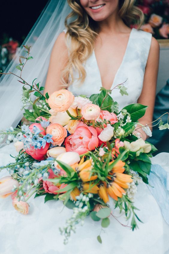 a colorful summer wedding bouquet of pink, orange, blush and blue blooms including peonies and greenery is chic