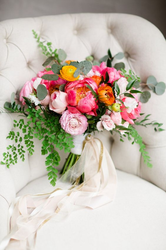 a colorful summer wedding bouquet with pink peonies, anemones and ranunculus, various types of greenery
