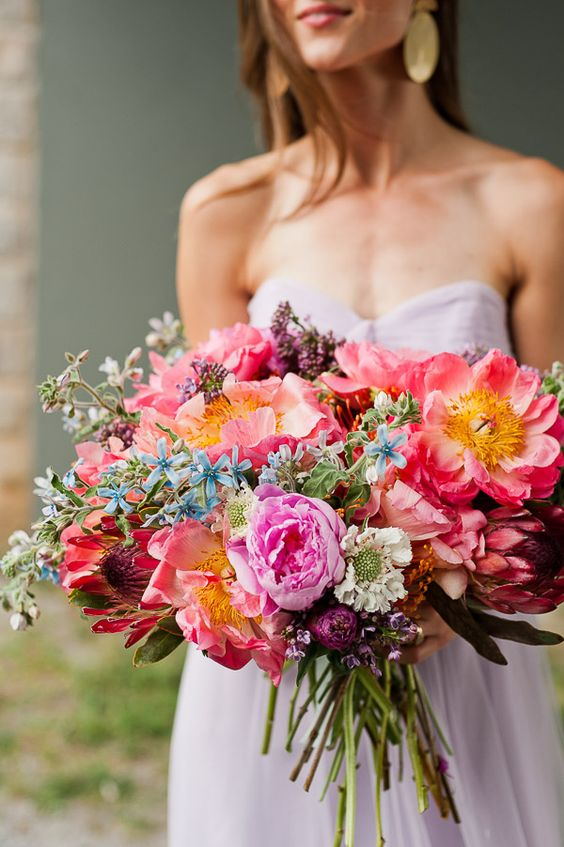 a colorful wedding bouquet of coral peonies, red and hot pink blooms, blue and neutral ones and lilac for a colorful wedding