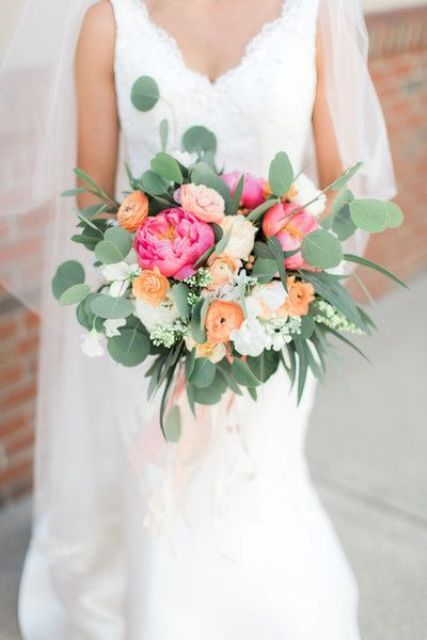 a colorful wedding bouquet of coral pink peonies, orange roses and white blooms plus eucalyptus is amazing for spring