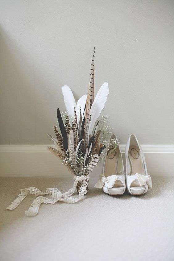 a cool feather and baby's breath wedding bouquet with a lace ribbon is a nice solution for a boho wedding