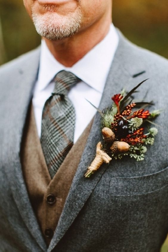 a cool rustic fall boutonniere with thistles, acorns, berries, greenery and rust blooms and wrap is a stylish idea