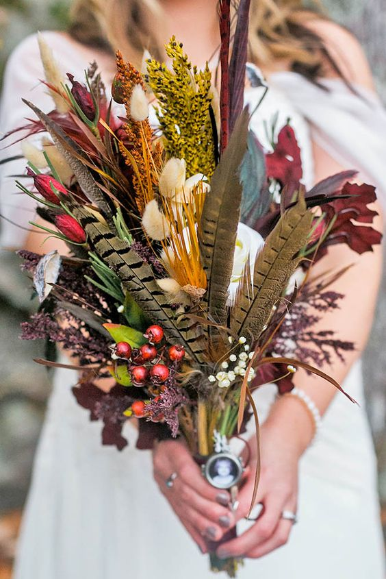 a creative boho wedding bouquet offeathers, colorful bynny tails, greenery and berries is a lovely and bold idea for a fall boho bride