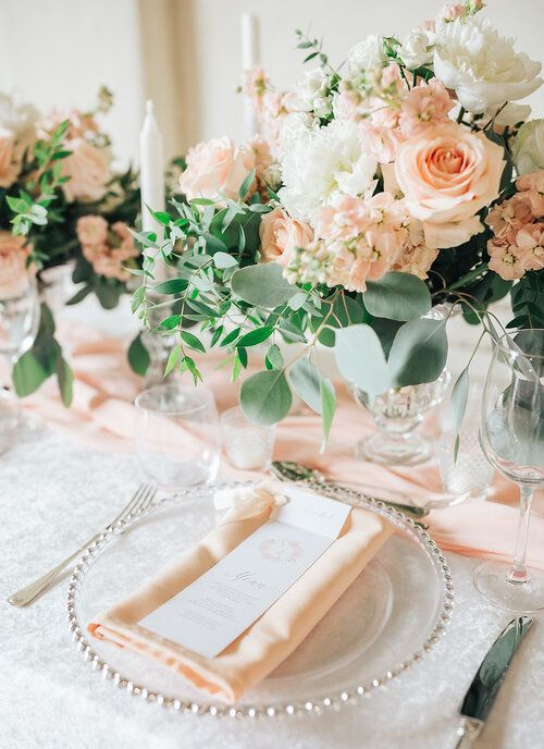 a delicate peach and cream wedding table setting with peachy and white blooms, peachy linens, white candles and greenery