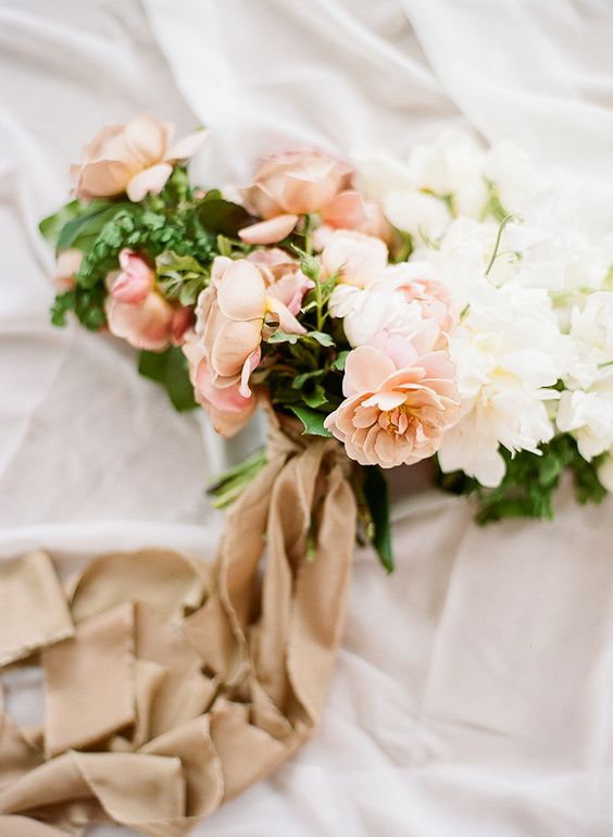 a delicate wedding bouquet with peachy and white blooms and greenery and tan colored ribbons is a beautiful idea
