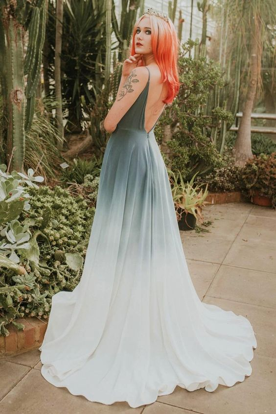 a dip dye green and white wedding dress with an open back, spaghetti straps and a train plus red hair