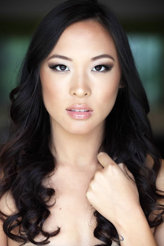 a dramatic Asian makeup with a glossy pink lip, dramatic smokeys, coral blushes and perfect skin