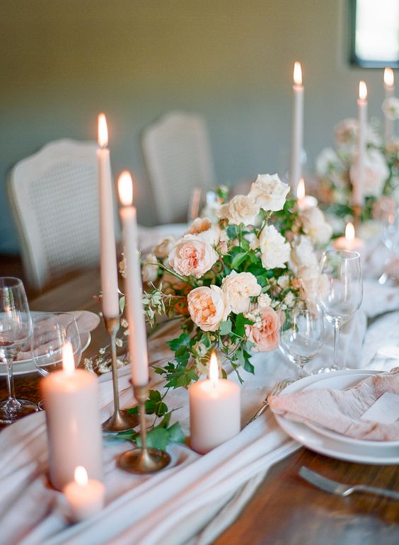 a dreamy wedding tablescape with a blush runner, peachy candles and napkins, greenery and white porcelain is chic