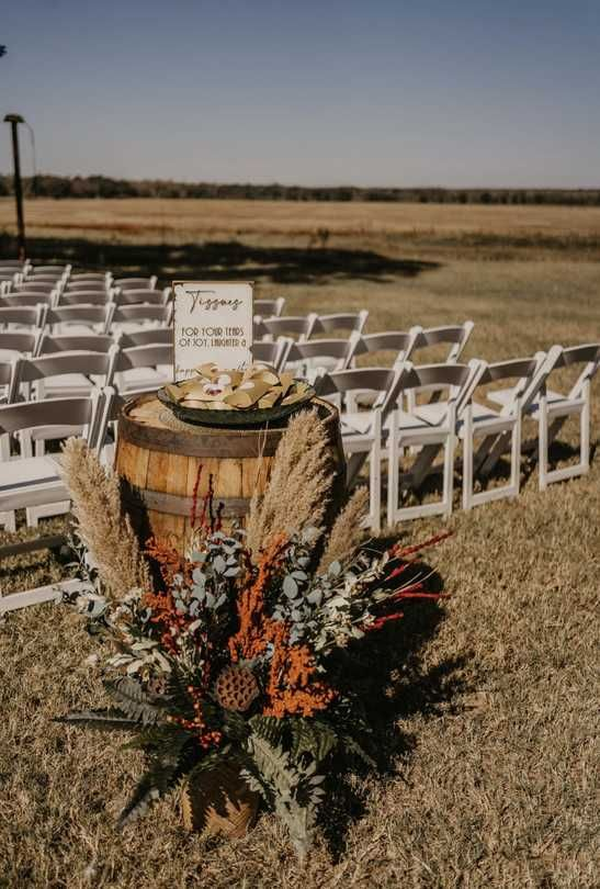 a fall aisle arrangement with pampas grass, greenery, fern, lotus and blooms is a stylish solution for a fall wedding
